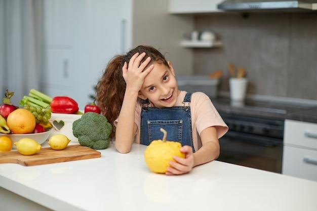 Vorderes porträt eines hübschen kleinen mädchens mit lockigem haar, das einen gelben kürbis hält und am tisch in der küche sitzt.