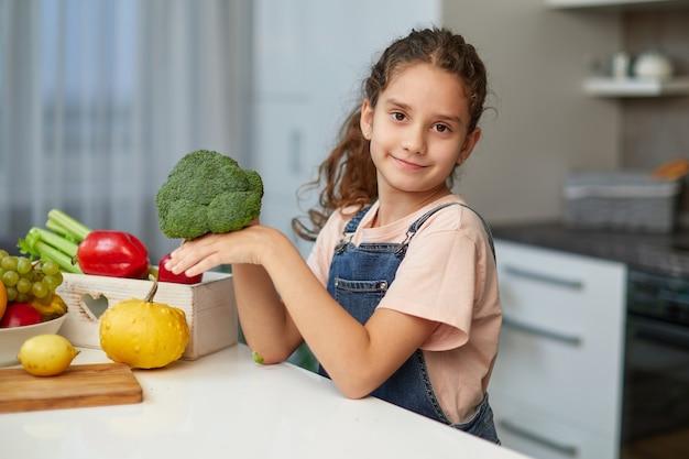 Vorderes porträt eines kleinen mädchens mit lockigem haar, das brokkoli hält und betrachtet, das am tisch in der küche sitzt.