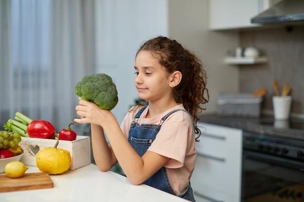 Vorderes porträt eines kleinen mädchens mit lockigem haar, das eine jeans und ein t-shirt trägt, brokkoli hält und betrachtet, am tisch in der küche sitzt.