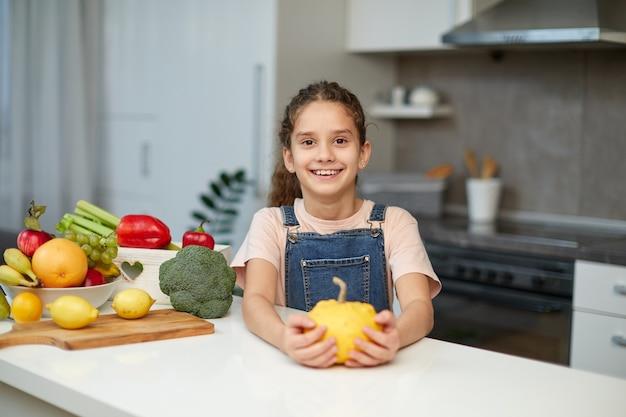 Vorderes porträt eines süßen kleinen mädchens mit lockigem haar, das eine jeans und ein t-shirt trägt, einen gelben kürbis hält und am tisch in der küche sitzt.