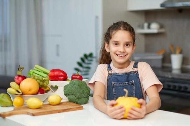 Vorderes porträt eines süßen kleinen mädchens mit lockigem haar, das einen gelben kürbis hält und am tisch in der küche sitzt.