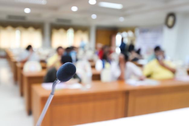 Vorderseite des mikrofons mit unscharfem hintergrund vieler leute auf der halle. mikrofon auf der bühne. aktivität indoor-konzept. seminar- oder tagungskonzept.