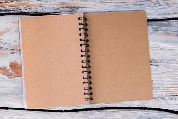 Vorderseite des notizbuchs aus recyceltem papier. leerer geöffneter notizblock auf weißem holz.