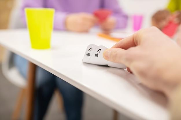 Vorfreude auf viel glück. finger der spielerhand, die halboffene karten betrachten, die während des spiels auf dem tisch liegen