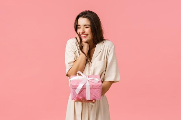 Vorfreude, feier und partykonzept. fröhliche schöne junge frau im kleid, jubelnde enge augen glücklich lächelnd und lachend, schönes geschenk empfangend, bekam hübsches geschenk, rosa hintergrund