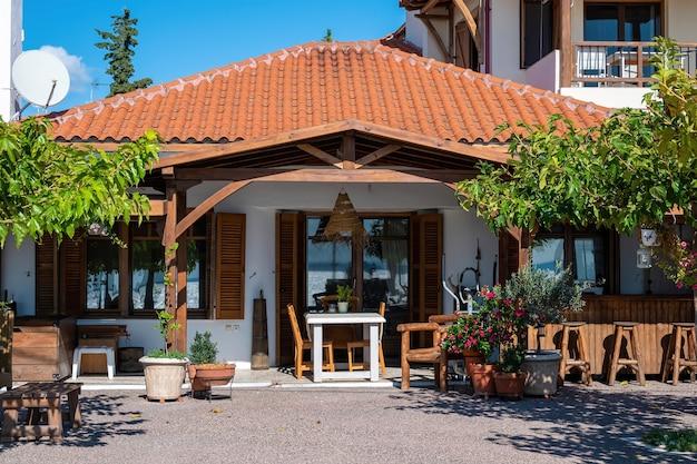 Vorgarten und terrasse eines restaurants im nationalen stil mit viel grün, stühlen und tischen in nikiti, griechenland