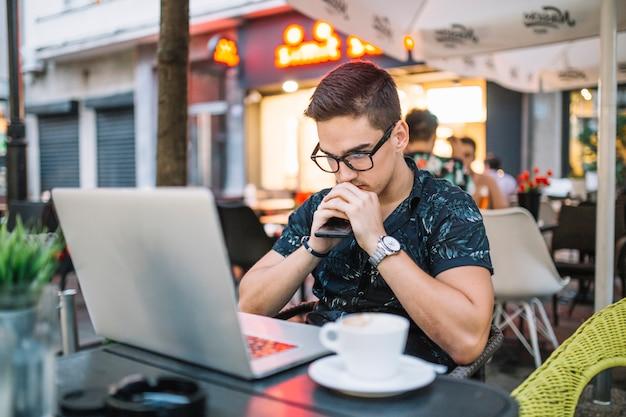 Vorgesehener junger mann, der in cafã sitzt