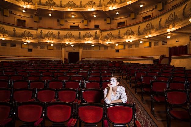 Vorgesehener weiblicher pantomime, der auf stuhl sitzt