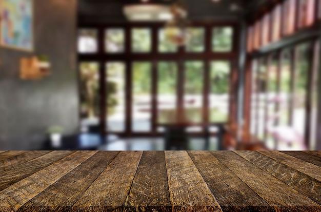 Vorgewählter fokus leeren braunen holztisch- und kaffeestube oder restaurantunschärfehintergrund