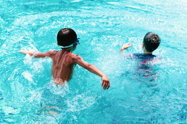 Vorgewählter junge des schwerpunkts kleiner junge des kopfes zwei, der im swimmingpool spielt