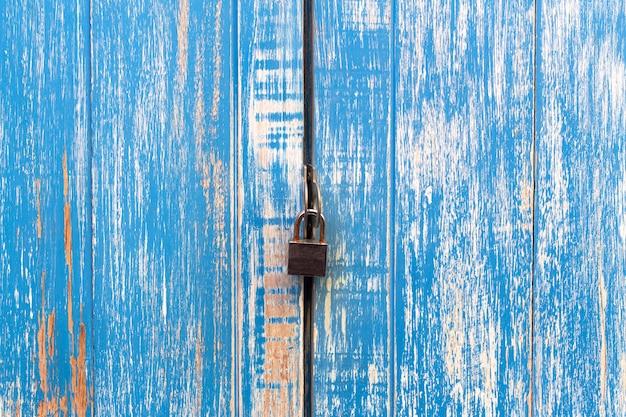 Vorhängeschloß auf blauem hölzernem wandhintergrund.