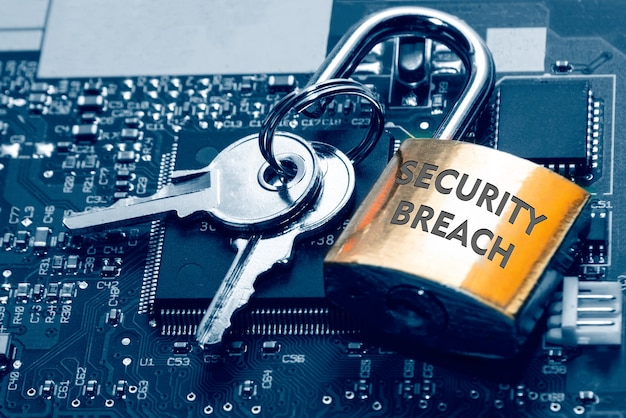 Vorhängeschloss mit der aufschrift eine sicherheitsverletzung und die schlüssel auf der platine. internet-computersicherheit und netzwerkschutzkonzept.
