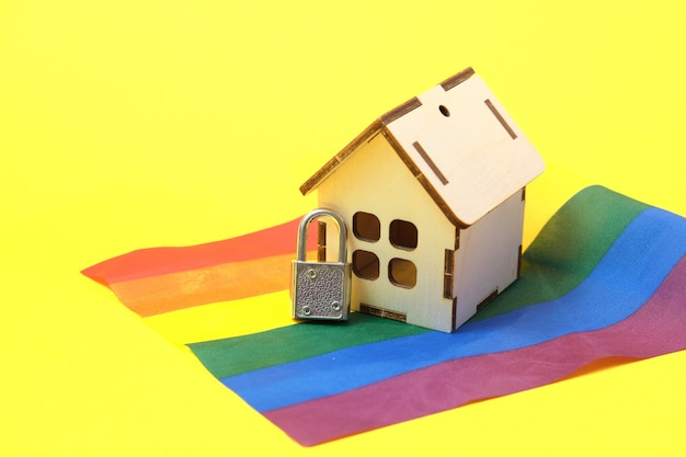 Vorhängeschloss und kleines haus auf der flagge der lgbt-gemeinschaft, sicherheit und privatsphäre des konzepts gleichgeschlechtlicher paare