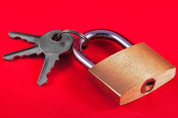 Vorhängeschloss und schlüssel auf rotem grund