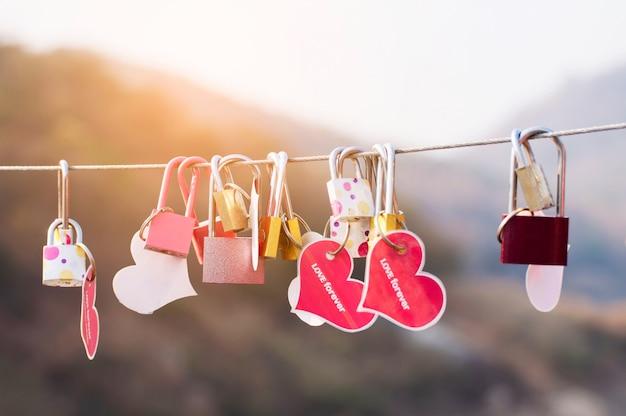 Vorhängeschlossschlüssel mit herzen der liebe auf brücke, kultur des liebeszeichensymbols