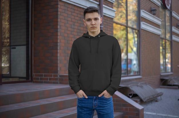 Vorlage eines schwarzen hoodies auf einem jungen mann, vorderansicht. präsentation modischer kleidung auf der straße. entwerfen sie freizeitkleidung für männer. mockup-hauben für die werbung im laden.