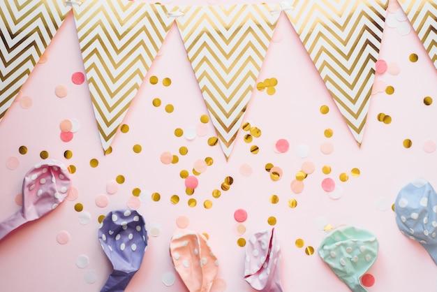 Vorlage für die feiertage. papiergirlande der flaggen auf einem rosa hintergrund mit konfetti und luftballons in pastellfarbe. feierlicher hintergrund, geburtstag