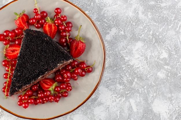 Vorne nahansicht köstlicher schokoladenkuchen in scheiben geschnitten mit schokocreme und frischen roten preiselbeeren