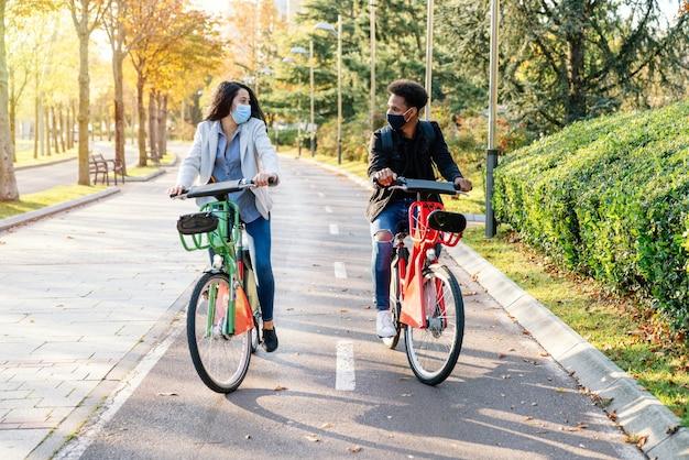 Vorne von zwei jungen mann und frau, die entlang eines radweges mit einem gemeinsamen elektrofahrrad in einem schönen park mit vielen bäumen bei sonnenuntergang fahren und eine gesichtsmaske für die 2020 coronavirus-pandemie tragen