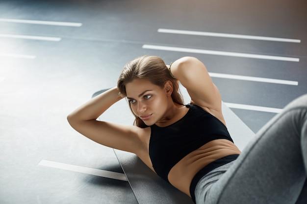 Vornehme junge frau, die bauchmuskeln knirscht, um ihren körper für den sommer vorzubereiten. fitness-konzept.