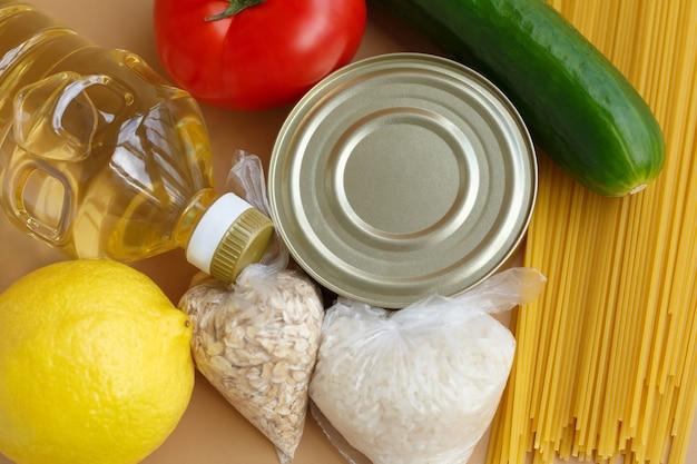 Vorrat an lebensmitteln. eine reihe von grundlagen für bedürftige. obst und gemüse, dosen und nudeln, öl und getreide