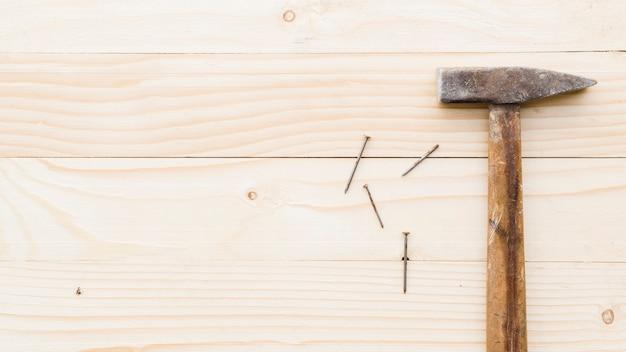 Vorschlaghammer mit nägeln auf tisch