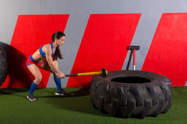 Vorschlaghammer tire hits frauentraining im fitnessstudio