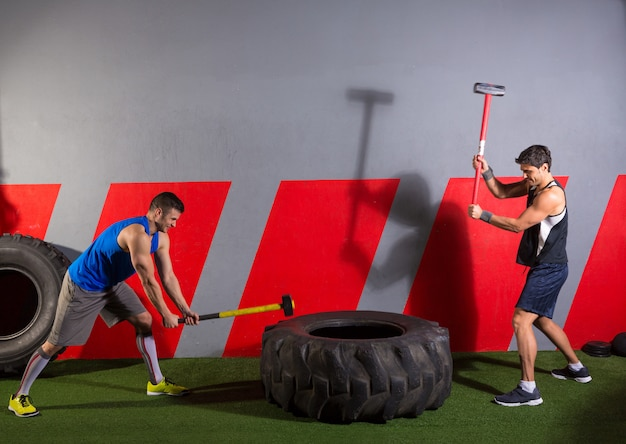 Vorschlaghammer tire hits manntraining im fitnessstudio