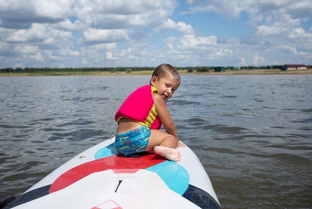 Vorschule glücklicher junge in schwimmweste - junger surfer lernen mit spaß auf surfbrett zu fahren. aktiver familienlebensstil, wassersportunterricht für kinder im freien
