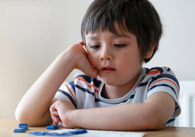 Vorschuljunge, der englisches upwords-spiel, intelligentes kind spielt upwords-spielbuchstaben mit elternteil zu hause spielt.