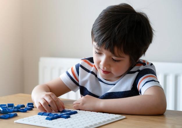 Vorschuljunge, der englisches upwords-spiel, kind zu hause spielt buchstabenspiel spielt.