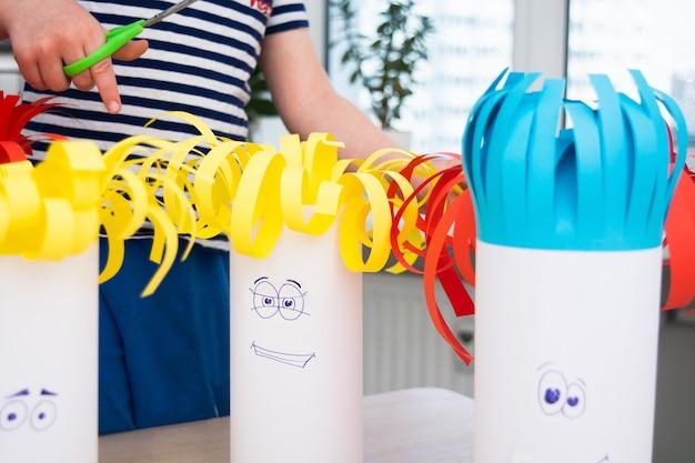 Vorschuljunge schneidet papierhaare mit einer schere auf handgemachten lustigen köpfen