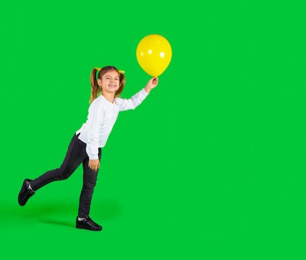 Vorschulkind, das mit dem beleuchtenden ballon auf spielt