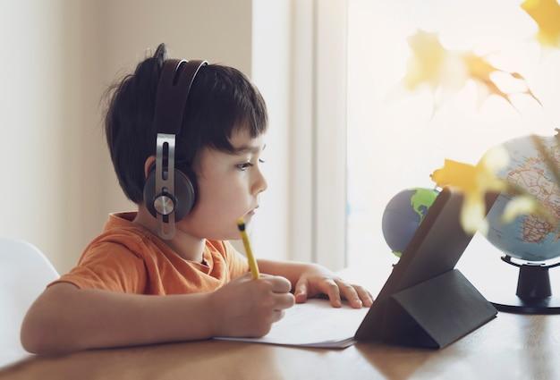 Vorschulkind, das tablet für seine hausaufgaben verwendet, kind, das kopfhörer trägt, das hausaufgaben macht, indem es digitale tablettensuchinformationen im internet verwendet, hausschulbildungskonzept, soziale distanzierung