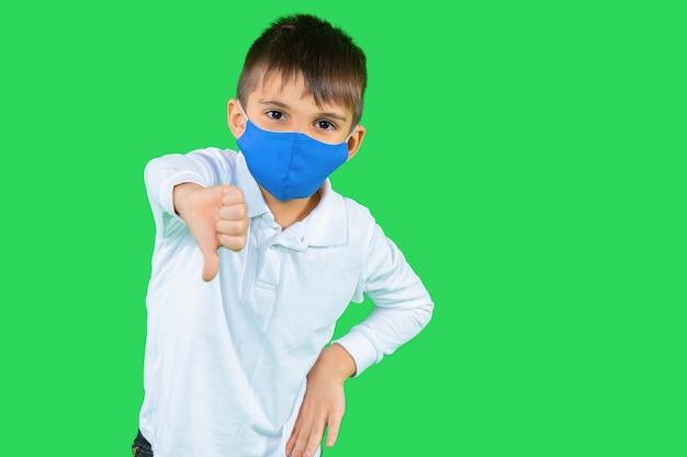 Vorschulkind in einer strapazierfähigen maske zeigen eine abneigung auf einem grünen isolierten hintergrund Premium Fotos
