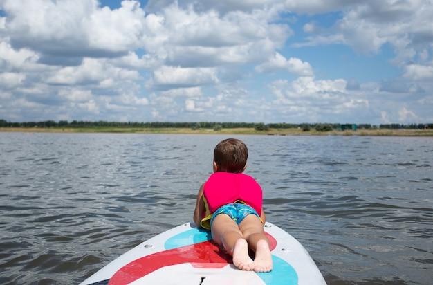 Vorschulkind in schwimmweste - junger surfer lernt mit spaß auf dem surfbrett zu fahren. aktiver familienlebensstil.