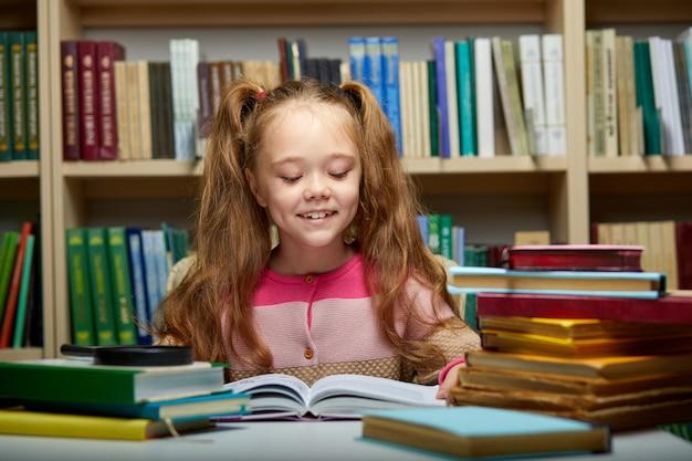Vorschulkind kleines mädchen liest ein buch in der bibliothek, kleines kaukasisches mädchen sitzt mit büchern in der nähe eines bücherregals