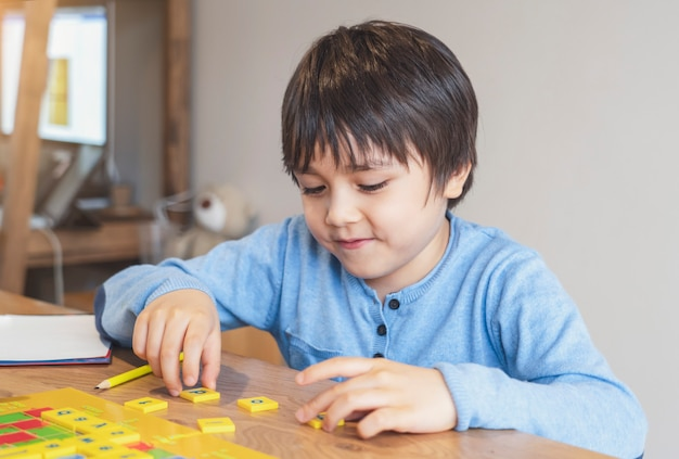Vorschulkind lernt englisches wortspiel, kindjunge konzentriert mit rechtschreibung englischen buchstaben mit elternteil zu hause. fernunterricht, aktivität für kinder zur heimschule während der selbstisolation