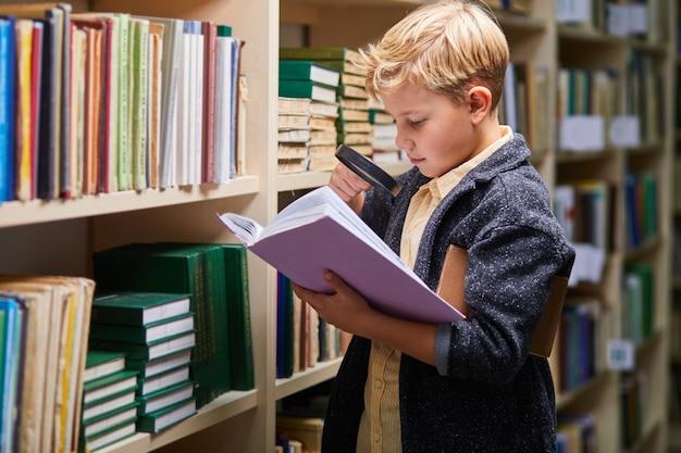 Vorschulkind liest buch in der bibliothek mit geduld, kaukasischer junge konzentriert sich auf bildung