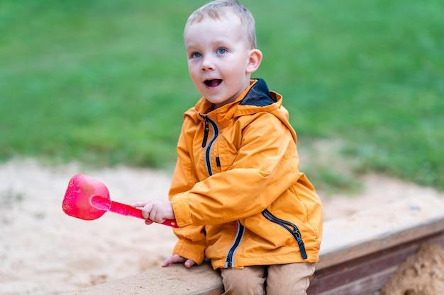 Vorschulkind sitzt im sandkasten und spielt mit der rosa spielzeugschaufel, die spielplatz genießt