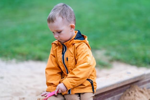 Vorschulkind sitzt im sandkasten