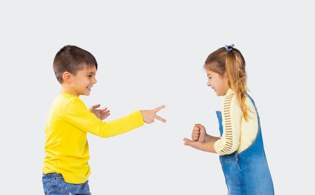 Vorschulkinder spielen ein spiel aus stein, schere, papier auf weißem grund. unterhaltungskonzept für kinder.
