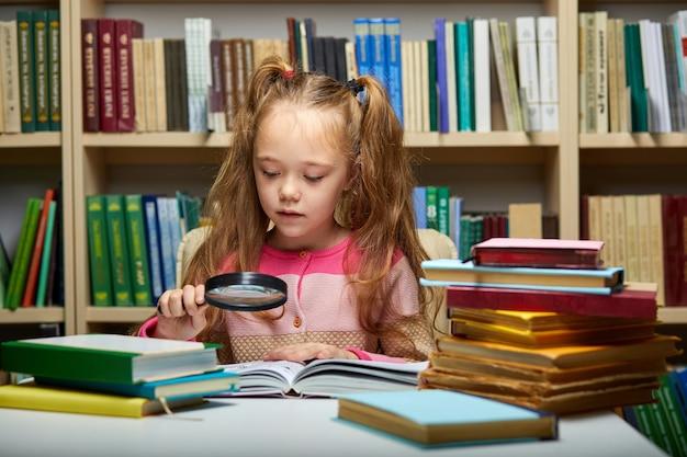 Vorschulmädchen liest buch in der bibliothek mit geduld, kaukasisches kind mädchen konzentriert sich auf bildung, wissen zu bekommen