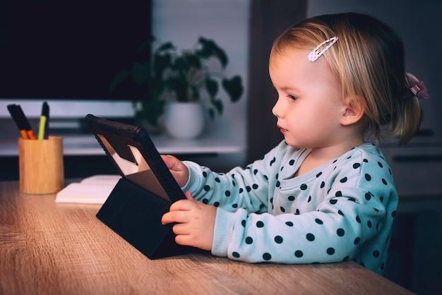 Vorschulmädchen mit tablet-pc zu hause kind mit digitaler technologie und internetkommunikation