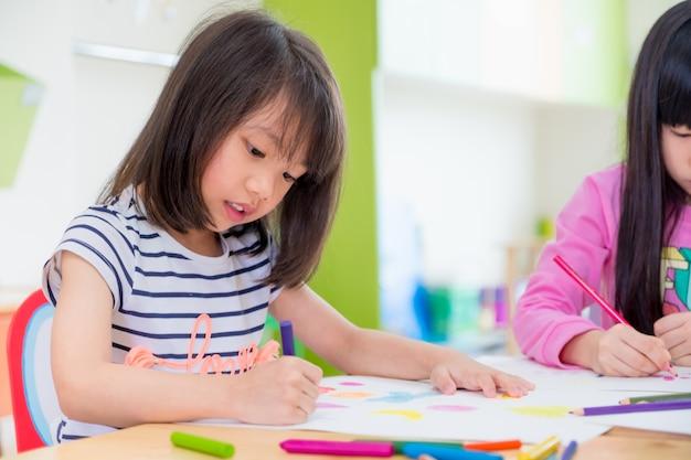 Vorschulmädchenkinderzeichnung mit farbbleistift auf weißbuch auf tabelle im klassenzimmer