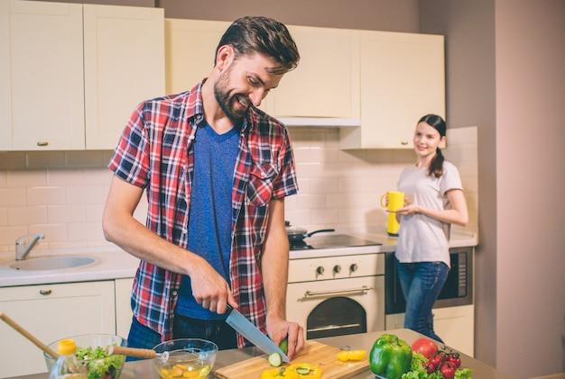 Vorsichtiger ehemann arbeitet in der küche. frau er ruht sich aus. er schneidet gurken in stücke. sie steht am herd und hält gelbe tasse. mädchen sieht ihn an. er lächelt und schaut nach unten.