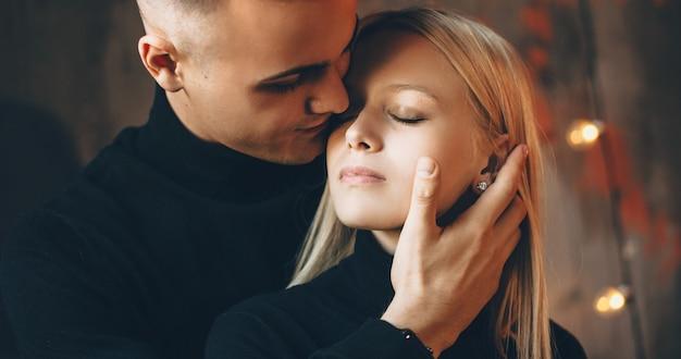 Vorsichtiger kaukasischer mann, der seine blonde frau umarmt und versucht, sie zu küssen, ihr gesicht berührend