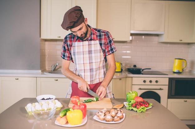 Vorsichtiger koch steht und gurke in stücke schneiden. er macht es mit messer. guy schaut runter. er ist ernst und konzentriert.
