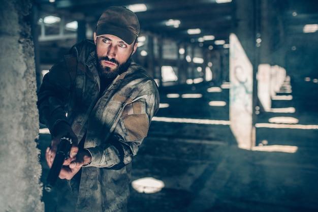 Vorsichtiger mann schaut gerade vorwärts. er steht hinter einer säule in einem großen hangar. warrior hat eine kleine schwarze waffe. er ist jederzeit schussbereit.
