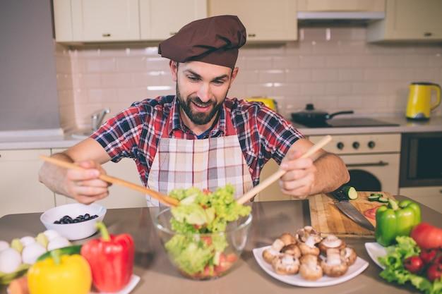 Vorsichtiger und konzentrierter mann steht am tisch und hält zwei holzlöffel. kerl mischt salat in der glasschüssel. es gibt verschiedene gemüsesorten auf dem tisch.